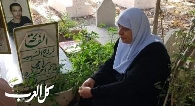 والدة الشهيد رامي غرّة تبكي أمام ضريح ابنها