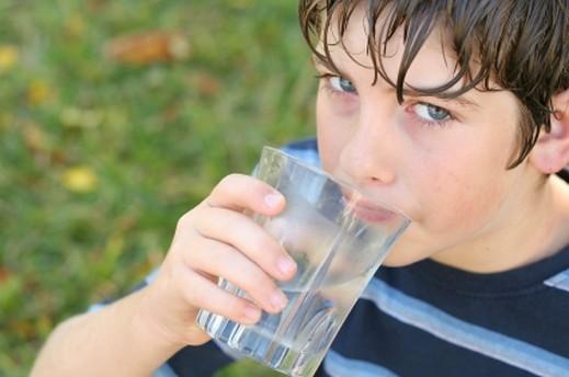 طفل يشرب ماء كرتون