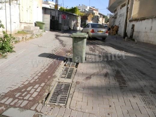 دلو النفايات يحمي السائقين في الطيبة من الوقوع بحفر الشوارع المنتشرة